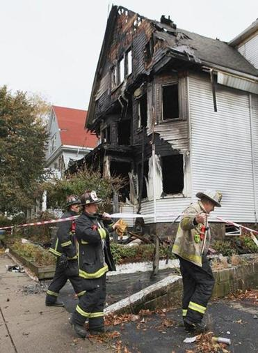 Firefighters conducted an investigation Saturday at the scene of a five-alarm blaze on Quint Avenue in Allston.