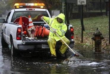 Department of Conservation and Recreation worker Larry Callanan cleared a storm drain on Mt. Auburn St. in Cambridge.