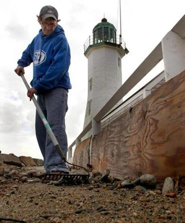Bob Gallagher clears rocks from the sidewalk near Old Scituate Light.