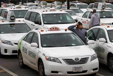 Dozens of drivers waited for fares in the taxi pool area at Logan International Airport.
