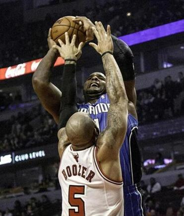 The Bulls' Carlos Boozer gets a fingertip on a shot by the Magic's Glen Davis, who hit just 7 of 22 shots.