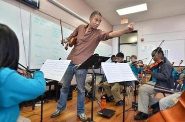 Adrian Anantawan, working with Conservatory Lab Charter School's young musicians, moved his left arm to mark the rhythm instead of using a baton.
