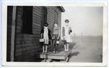 In Lakin, Kansas, three children prepared to leave for school wearing goggles and homemade dust masks to protect them from the dust in 1935.