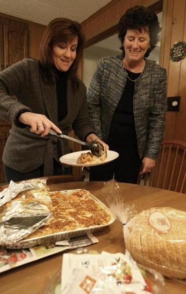 Gayle Cipitelli (left) drops off a meal at the home of Doug and Patty Oakley,