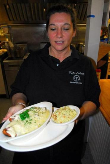 Owner Leanne Hunt serves an entree of chicken parmesan. Below, an order of baked haddock.