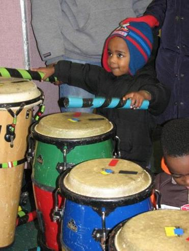 Jordyn Arnold, 3, of Holbrook, tried his hand at drumming at Turner Free Library during Saturday's Winterfest in Randolph. At left, library assistant Denise Costa, as Mrs. Claus, entertained children in attendance.