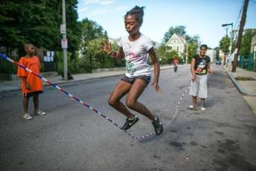 Kaori Tate, 10, jumps rope outside the garden at a block party before Labor Day. The track athlete is about to start sixth grade, and she has her new Air Jordans, gray and purple, ready.