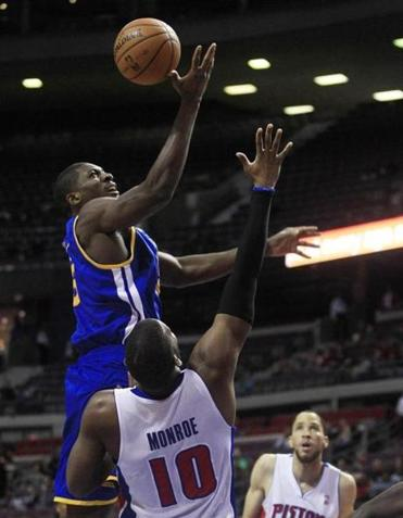 Warriors' Festus Ezeli shoots over Greg Monroe, as the Pistons' home win streak ended.