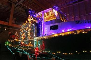 Jay Walsh looks out from his elaborately decorated lobster boat, complete with orange, lobster-shaped lights in a trap, that he will be showing off at this year's parade.