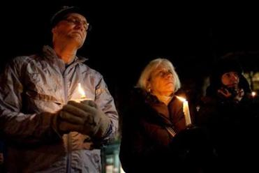Tom Estabrook, Brenda Steinberg, and Laura V. Cantera attended a candlelight vigil in Somerville's Davis Square.