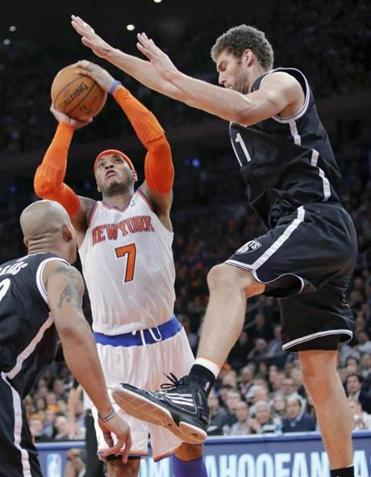 Carmelo Anthony drives through Nets defenders Keith Bogans (left) and Brook Lopez.