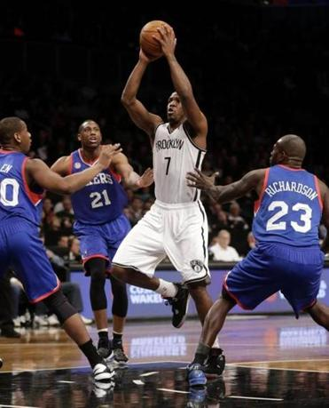 Brooklyn's Joe Johnson took it to the hoop early against the Sixers — despite three defenders in his path.