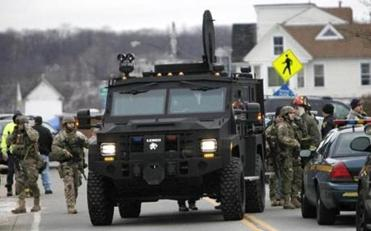 A Lenco Monroe County Sheriff's Department armored truck dropped off residents who were evacuated from the neighborhood, in Webster, N.Y. Dec. 24 after a former convict set a house and car ablaze ito lure firefighters, then opened fire on them, killing two.