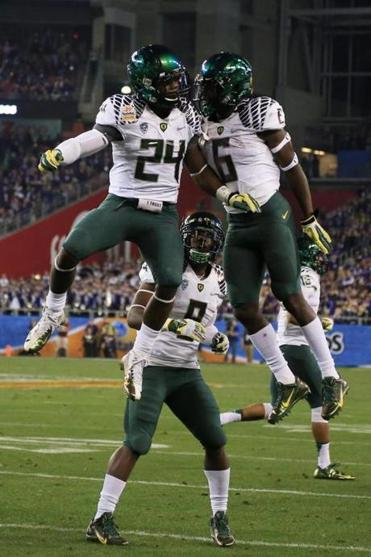 Kenjon Barner, left, celebrated his second quarter touchdown with DeAnthony Thomas, right, and Byron Marshall, center, of the Oregon Ducks during the Tostitos Fiesta Bowl against the Kansas State Wildcats at University of Phoenix Stadium on January 3, 2013 in Glendale, Arizona.