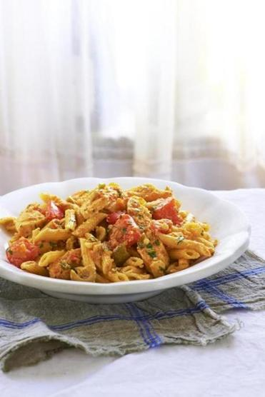Pasta tossed with chicken, olives, and almond red pepper sauce.