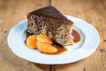 A slice of the sticky toffee pudding with satsuma mandarin oranges prepared by pastry-chef couple Molly Hanson and Kate Henry in their Concord kitchen.