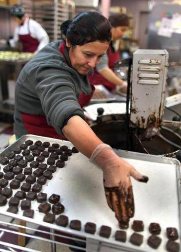 Preparing for Valentine's Day, Serenade's busiest time of the year, Liliana Topjanasi works at the Brookline shop to make hand-dipped chocolates.