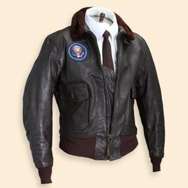 "President Kennedy's Air Force One bomber jacket with the presidential seal is expected to bring $20,000-$40,000 at John McInnis's auction next Sunday of David F. Powers's collection of JFK personal and political items. The two were friends from the beginning of Kennedy's political career in Boston until the day he died in Dallas. Banner flag ""Céad Míle Fáilte"" (in Irish, ""a hundred thousand welcomes""), with Kennedy pictured between the US and Irish flags from his June 1963 visit to Ireland, has a $500-$1,000 estimate. Sterling silver inaugural lapel pin has a $150-$300 estimate. ""The President's Special Award,"" which Kennedy signed and gave in jest to his confidant Powers for drinking his ""Heinkens'' beer, has a $5,000-$10,000 estimate. Mahogany veneer desk used by Powers at the White House is expected to bring $5,000-$10,000."