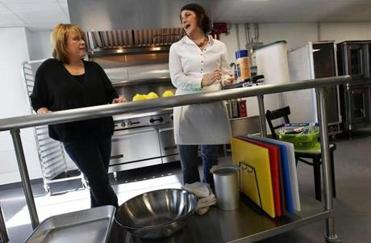 Lisa Sutton, left, owner of Kitchen Local, talked with Katie Habib, right, owner of Habib's Home Cooking in Newburyport, in the catering kitchen section of Kitchen Local.