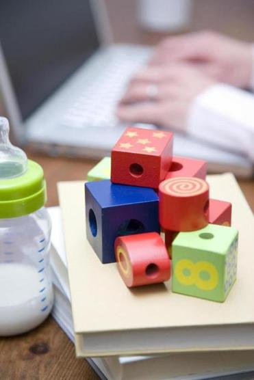 Close up shot of baby blocks and bottle on books. In background are the hands of a mother working on her computer