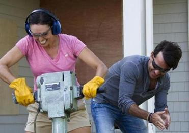 "As host of HGTV's ""Spontaneous Construction,"" Ricky Paull Goldin supervises Robin St. John as she jackhammers at her parents' Osterville home during taping of an episode."