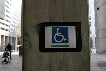A handicap sign is held up with electrical tape