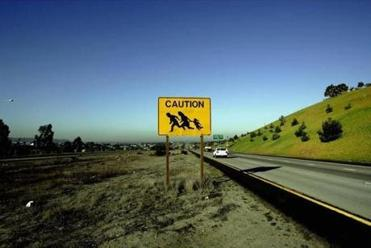 A sign on a freeway warned drivers of people crossing in Chula Vista California