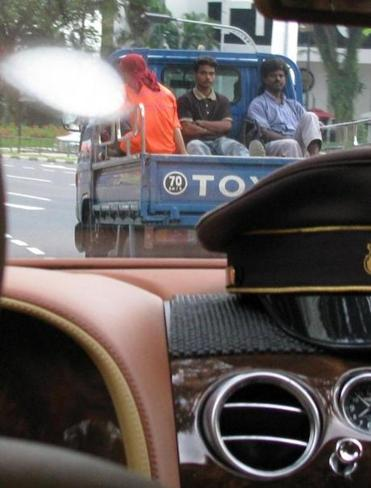 In Singapore, three men in a work vehicle beginning a long day in tropical heat, viewed from a chauffeur-driven Bentley.