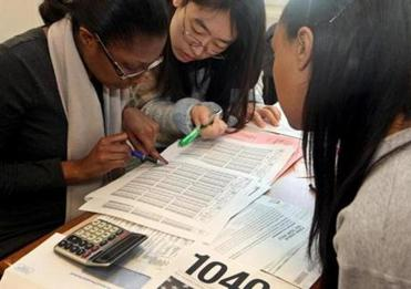 Volunteers Carla Daley (left) and Ziyi Lou (middle) helped Kijana Rose (right) with her taxes, using the paper forms.
