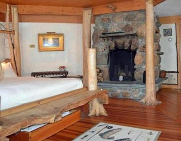 20tank - The whimsical Trout Room at the Pitcher Inn has a tree-trunk bed frame and river stone fireplace. (Pamela Wright)