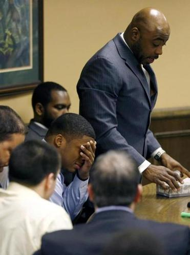 Ma'lik Richmond covered his eyes as his attorney Walter Madison, standing, asked the court for leniency after Richmond and co-defendant Trent Mays, lower left, were found delinquent on rape and other charges after their trial in juvenile court in Steubenville, Ohio.