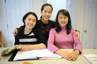 Carolyn Zhou (left, 15) sits with her sister Megan (middle , 14) and their mom Jianlin Li with homework at the kitchen table.