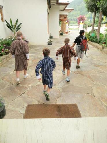 The author's sons, Brendan, Aidan, and Evan Glenn, wearing the national dress, and the family's driver, Kezang, right, head for school.