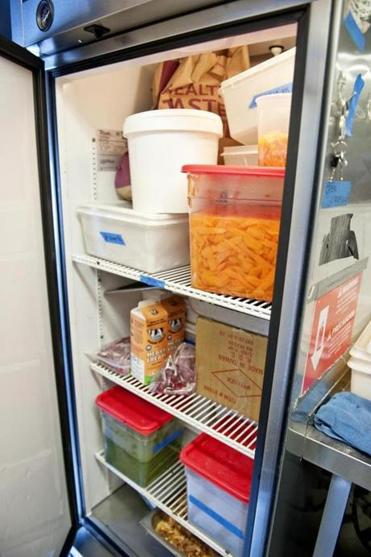 One of two refrigerators aboard holds herbs, veggies, garnishes, sauces, and other supplies.