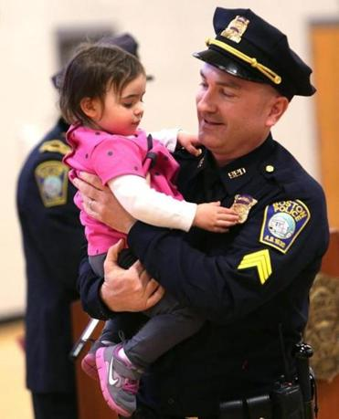 Sergeant Edward T. Norton, with his daughter Maren, 2, was promoted Thursday. He was honored for heroism in December after leaping into Boston Harbor to save a woman.