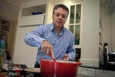 "Dr. Keith Stuart stirs the dish, ""African Peanut Stew."""