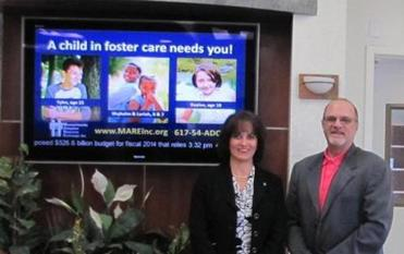 Joanne Tully, Braintree Cooperative Bank Vice President, and Paul Deletetsky, Mass. Adoption Resource Exchange (MARE) Board of Directors, with the Bank's video screen encouraging customers to learn about adopting a local child from foster care.