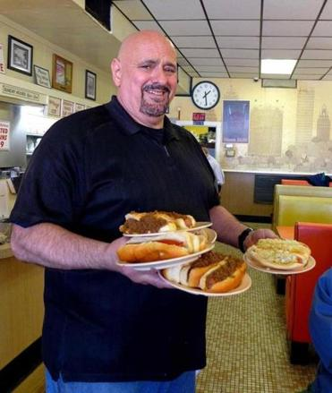 "Olneyville New York System manager Jimmy Saccoccio brings a dozen hot wieners (some ""all the way"") to a table of four patrons."