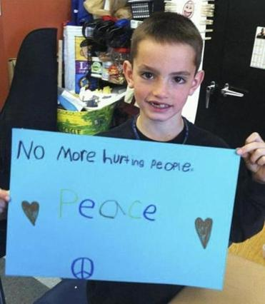 "In the popular photograph, Martin was shown holding a sign that read: ""No more hurting people. Peace."""