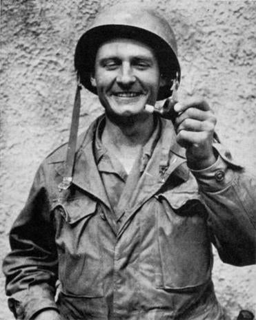 Father Emil Kapaun holds a broken pipe in an undated photo. He was posthumously awarded the Medal of Honor this month.