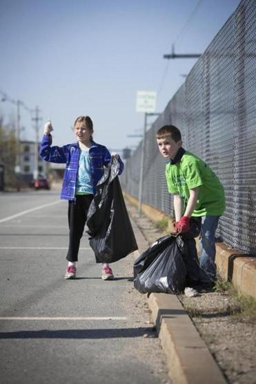 Caroline Moore, 10, requests a honk from a trucker while picking up trash with her brother John, 8, during the townwide clean-up day.