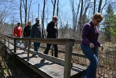 "Sarah Buck of Manchester, right, crosses a boardwalk with a group on the Manchester-Essex Conservation's ""The Big Walk"" through the conservation land."