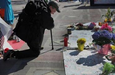 Scott MacGregor (above) of Boston stopped to pray at the memorial set up in Copley Square.