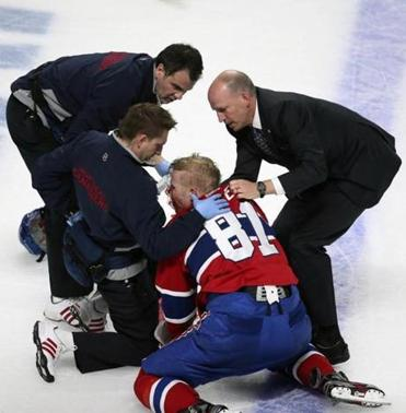 Lars Eller of the Canadiens is helped after slamming face-first into the ice following a hit by Ottawa's Eric Gryba.
