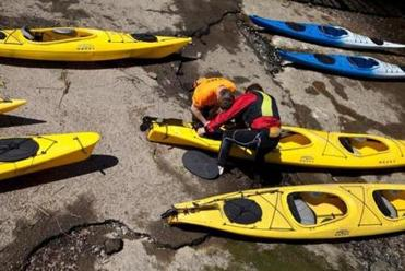 "Kayak guides John Vogl (left) and Eli Cutting prepared kayaks for guests before the Plum Island Kayak ""Seal Paddle"" trip."
