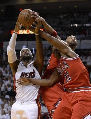 The Heat's LeBron James tries to fend off Taj Gibson and Jimmy Butler (21).