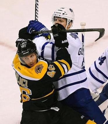 David Krejci and Maple Leafs defenseman Carl Gunnarsson fight for position in front of the Toronto net in the first.