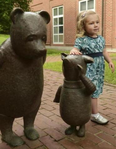 June Henry, 3, of Newton with the new sculpture of Piglet, alongside Pooh, at the Newton Free Library.