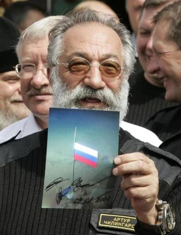 Arctic explorer Artur Chilingarov held a photograph showing the Russian national flag on the seabed at the North Pole.