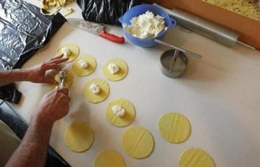 Pasta shop owner Jean Louis Faber making ravioli .